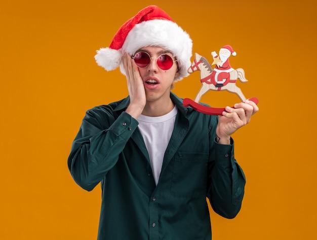 Zaniepokojony młody blondyn w kapeluszu i okularach świętego mikołaja, trzymający mikołaja na figurce konia na biegunach, patrząc na kamerę trzymając rękę na twarzy na białym tle na pomarańczowym tle