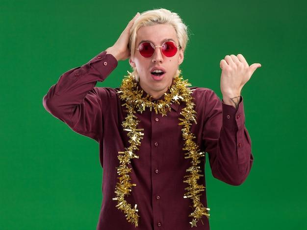 Zaniepokojony młody blondyn w okularach z girlandą świecidełka na szyi, trzymając rękę na głowie wskazującą na bok na białym tle na zielonej ścianie