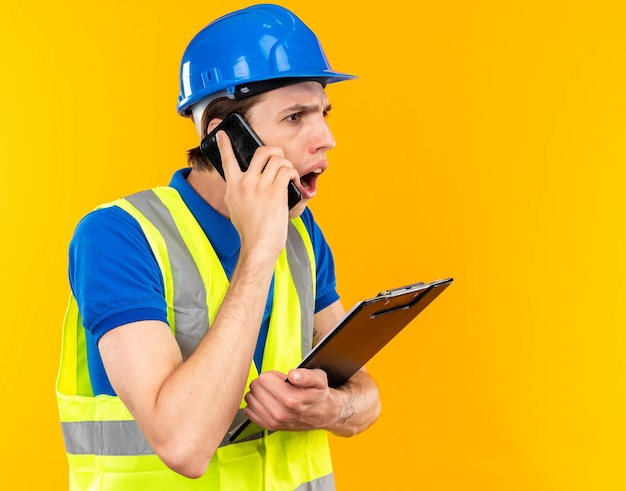 Zaniepokojony młody budowniczy mężczyzna w mundurze trzymającym schowek mówi przez telefon
