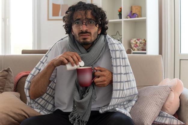 Zaniepokojony młody chory kaukaski mężczyzna w okularach optycznych, owinięty w kratę z szalikiem na szyi, trzymający kubek i butelkę z lekarstwami, siedzący na kanapie w salonie