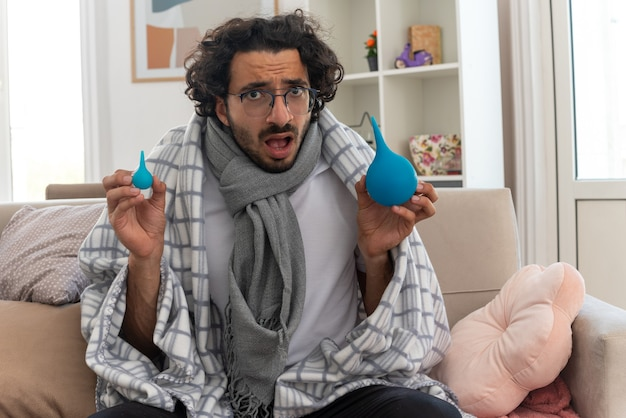 Zaniepokojony młody chory kaukaski mężczyzna w okularach optycznych, owinięty w kratę z szalikiem na szyi, trzymający lewatywy, siedzący na kanapie w salonie