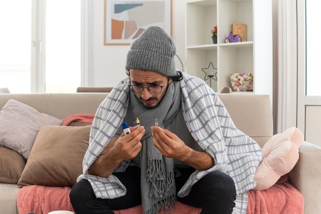 Zaniepokojony młody chory kaukaski mężczyzna w okularach optycznych owinięty w kratę z szalikiem na szyi w czapce zimowej trzymający strzykawkę z termometrem i ampułkę medyczną siedząc na kanapie w salonie