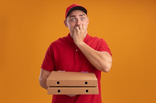 Zaniepokojony młody człowiek dostawy ubrany w mundur z czapką, trzymając pudełka po pizzy, kładąc dłoń na ustach odizolowanych na pomarańczowej ścianie