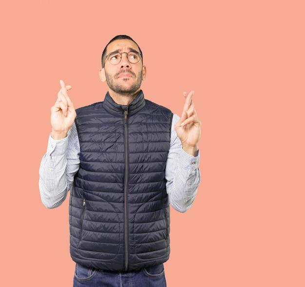Zaniepokojony młody człowiek robi gest skrzyżowanymi palcami