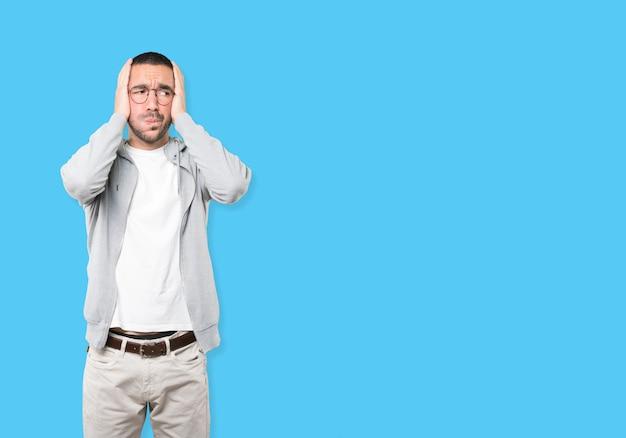Zaniepokojony młody człowiek robi gest ulgi