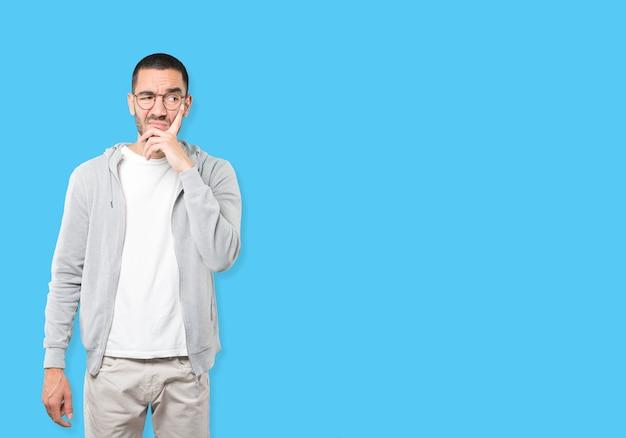 Zaniepokojony młody człowiek robi gest wątpliwości