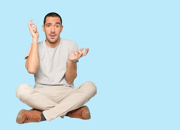 Zaniepokojony młody człowiek robi gest zmieszania