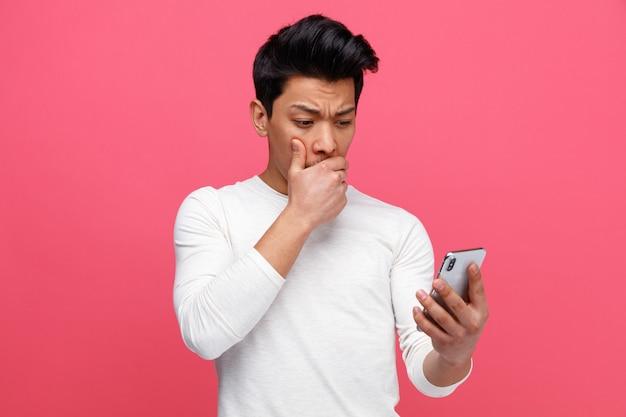 Zaniepokojony młody człowiek trzyma telefon komórkowy i patrząc na niego, trzymając rękę na ustach