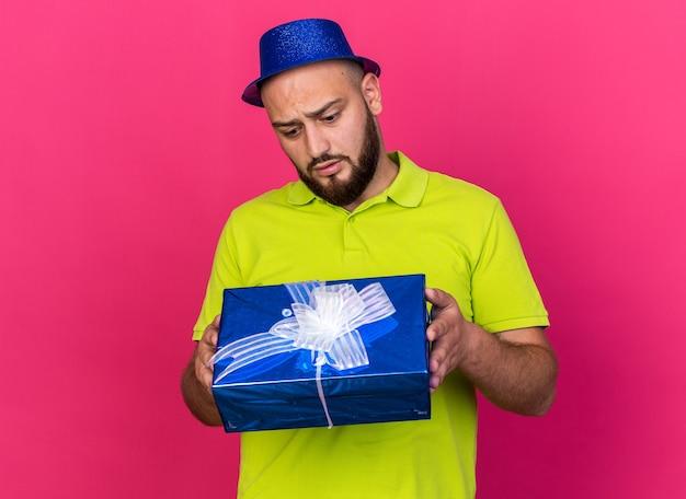 Zaniepokojony młody człowiek ubrany w niebieską imprezową czapkę, trzymający i patrzący na pudełko na prezent na różowej ścianie