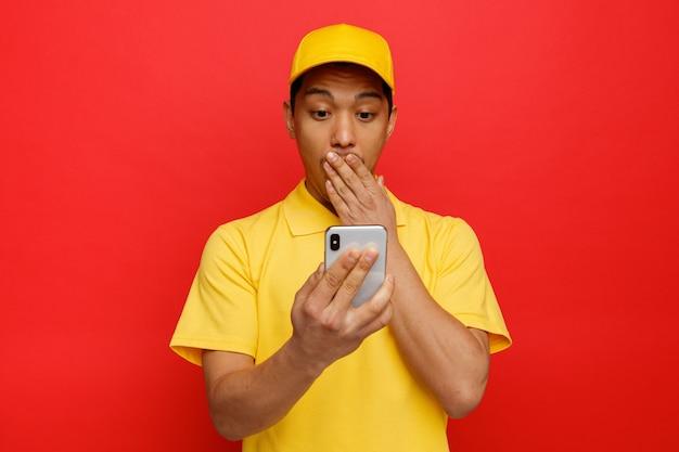 Zaniepokojony młody człowiek w czapce i mundurze, trzymając i patrząc na telefon komórkowy robi gest ups