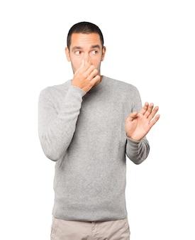 Zaniepokojony młody człowiek z gestem obrzydzenia