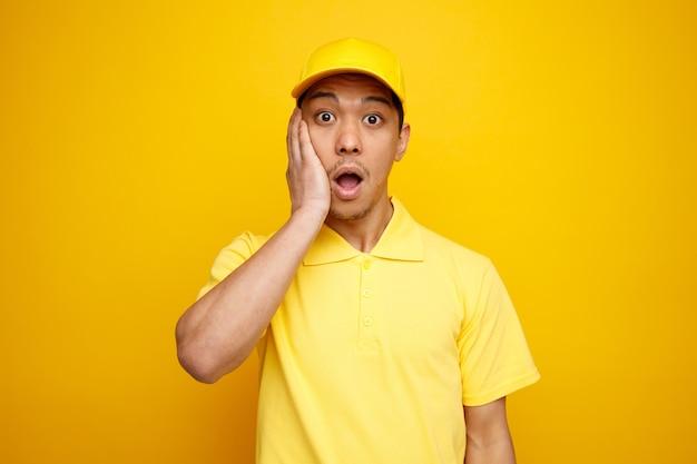 Zaniepokojony młody dostawca ubrany w czapkę i mundur, trzymając rękę na twarzy