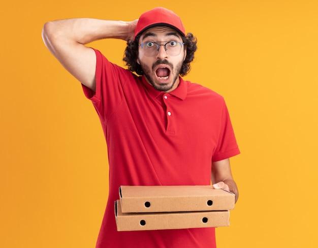 Zaniepokojony młody kaukaski mężczyzna dostawy w czerwonym mundurze i czapce w okularach trzymających paczki pizzy, trzymając rękę na głowie odizolowaną na pomarańczowej ścianie z miejscem na kopię