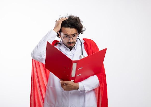 Zaniepokojony młody kaukaski mężczyzna w okularach optycznych w mundurze lekarza z czerwonym płaszczem i stetoskopem na szyi kładzie rękę na głowie, trzymając i patrząc na folder plików z miejscem na kopię