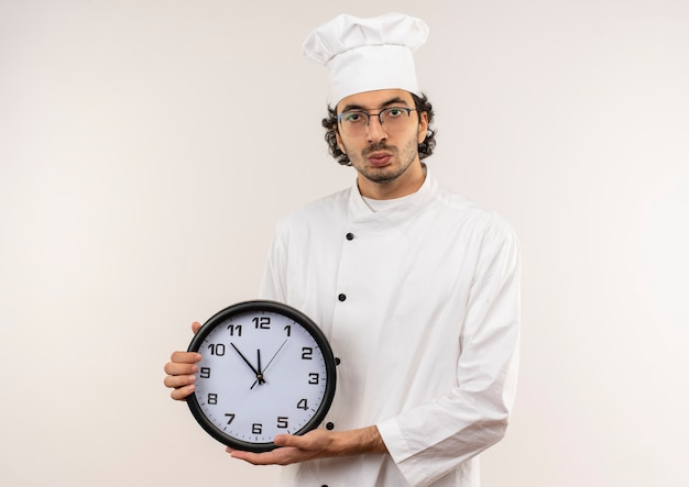Zaniepokojony młody kucharz mężczyzna w mundurze szefa kuchni i okularach trzyma zegar ścienny