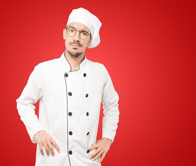 Zaniepokojony młody kucharz robi gest wątpliwości