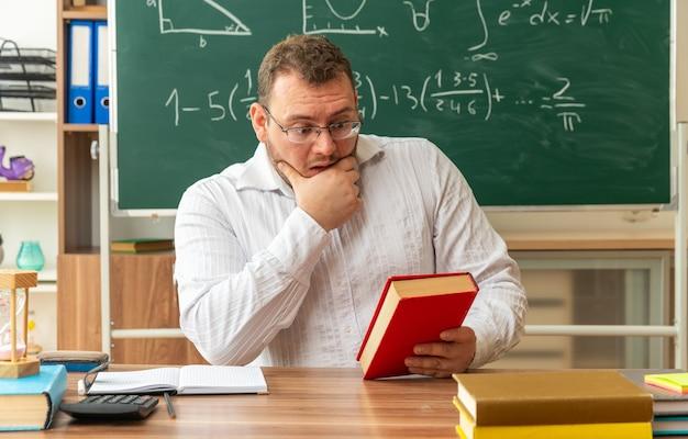 Zaniepokojony młody nauczyciel w okularach siedzi przy biurku z przyborami szkolnymi w klasie, trzymając i patrząc na zamkniętą księgę trzymając rękę na brodzie