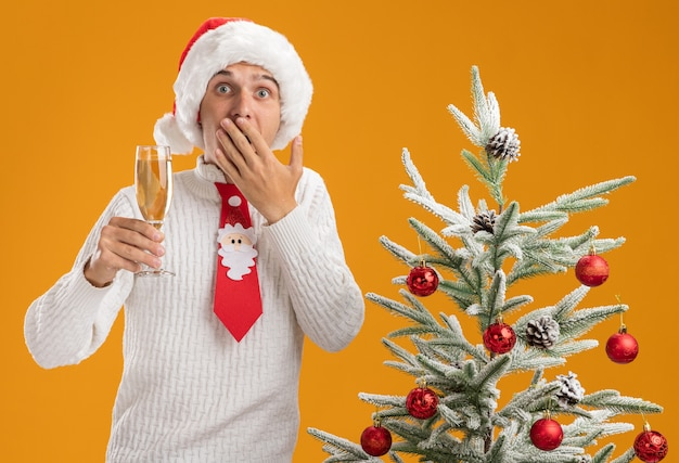Zaniepokojony młody przystojny facet w świątecznym kapeluszu i mikołajowym krawacie stojący obok udekorowanej choinki trzymający kieliszek szampana trzymający rękę na ustach patrzący na pomarańczową ścianę