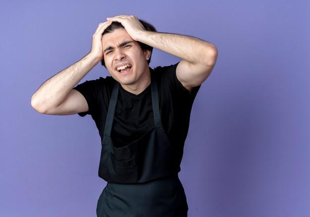 Zaniepokojony młody przystojny fryzjer w mundurze chwycił głowę na niebiesko
