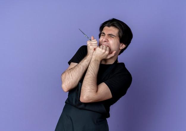Zaniepokojony młody przystojny mężczyzna fryzjer w mundurze, trzymając nożyczki i gryzie pięść