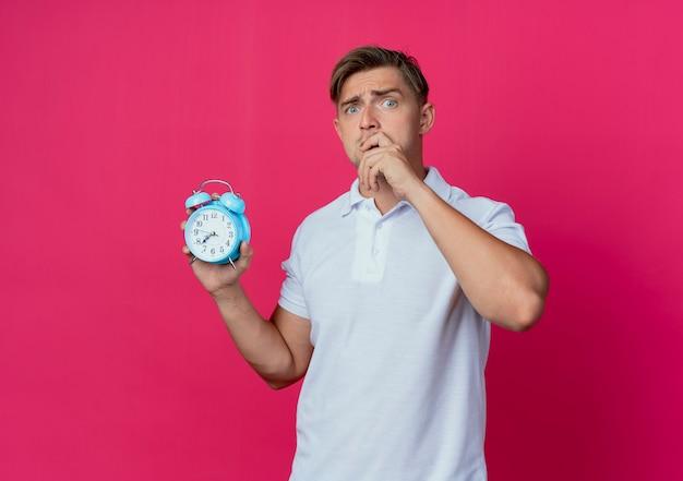 Zaniepokojony młody przystojny student płci męskiej trzymając budzik na białym tle na różowej ścianie