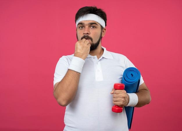 Zaniepokojony młody sportowy mężczyzna noszący opaskę i opaskę na nadgarstek, trzymając hantle z matą do jogi, kładąc rękę na brodzie