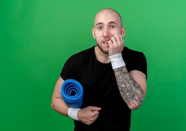 Zaniepokojony młody sportowy mężczyzna ubrany w opaskę, trzymając matę do jogi i gryzie paznokcie na białym tle na zielonej ścianie