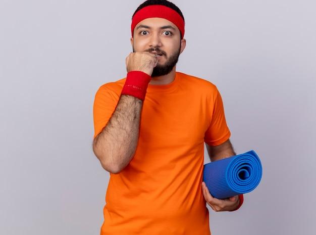 Zaniepokojony młody sportowy mężczyzna z opaską na głowę i nadgarstkiem trzymając matę do jogi, kładąc pięść na brodzie