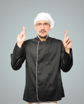 Zaniepokojony młody szef kuchni robi gest skrzyżowanymi palcami
