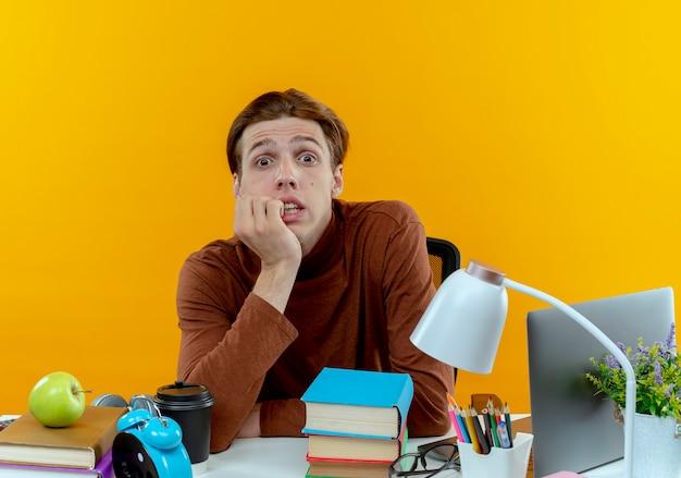 Zaniepokojony młody uczeń chłopiec siedzi przy biurku z narzędziami szkolnymi gryzie paznokcie