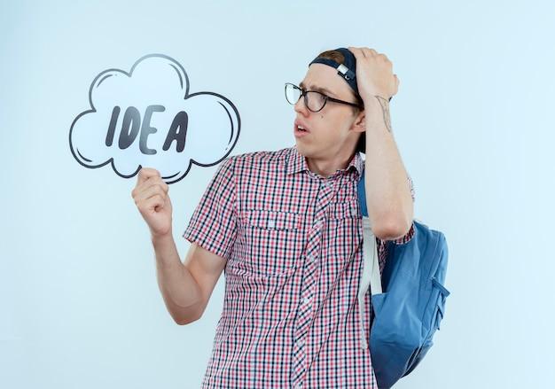 Zaniepokojony młody uczeń chłopiec ubrany w plecak, okulary i czapkę, trzymając i patrząc na bańkę pomysłów i kładąc rękę na głowie