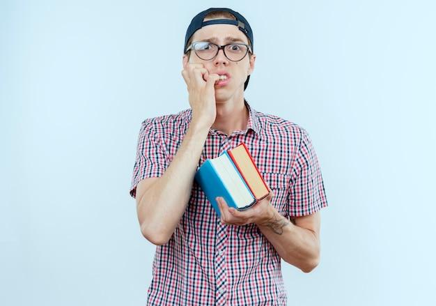 Zaniepokojony młody uczeń, ubrany w plecak, okulary i czapkę, trzymający książki i obgryza paznokcie
