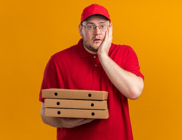 Zaniepokojony nadwagą młody doręczyciel w okularach optycznych, trzymając pudełka po pizzy i kładąc dłoń na twarzy odizolowanej na pomarańczowej ścianie z miejsca na kopię
