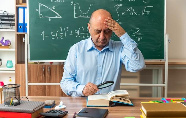 Zaniepokojony nauczyciel w średnim wieku siedzi przy stole z przyborami szkolnymi, czytając książkę z lupą, kładąc rękę na głowie w klasie