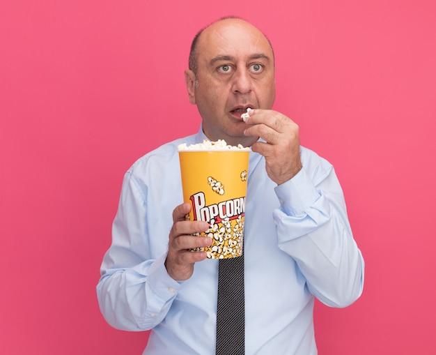 Zaniepokojony patrząc na bocznego mężczyznę w średnim wieku noszącego białą koszulkę z krawatem, trzymającego i próbującego wiadra popcornu na różowej ścianie