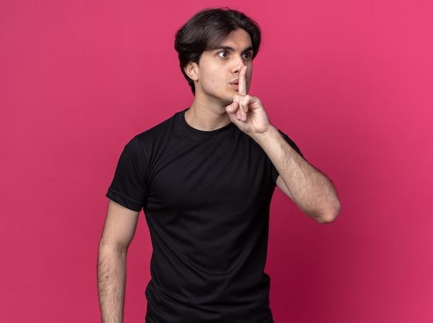 Zaniepokojony patrząc na bok młody przystojny facet ubrany w czarną koszulkę pokazujący gest ciszy na różowej ścianie