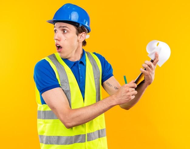 Zaniepokojony patrząc z boku młody budowniczy mężczyzna w mundurze trzymającym schowek