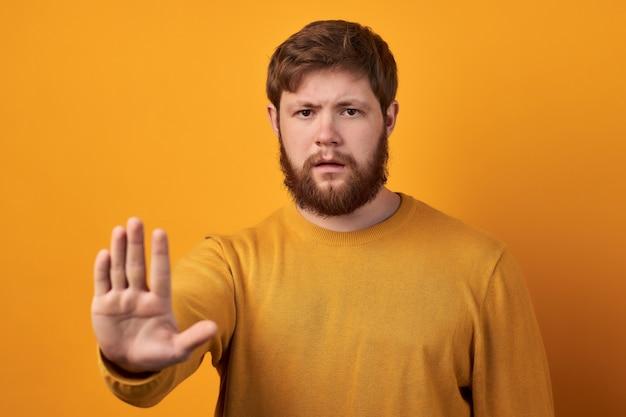 Zaniepokojony poważny brodaty mężczyzna w okrągłych okularach wyciąga dłoń w stronę aparatu