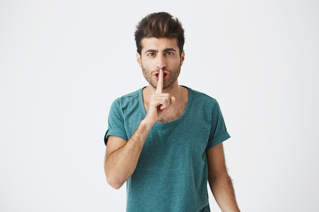 Zaniepokojony poważny mężczyzna w zwykłej koszulce, trzymający palec wskazujący na ustach, proszący o milczenie i nie hałasowanie. wyraz twarzy
