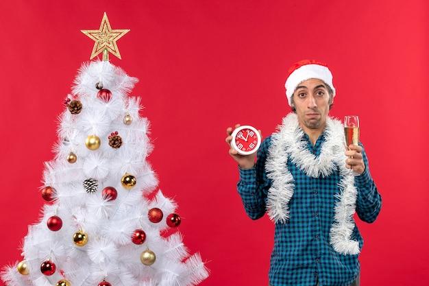 Zaniepokojony smutny młody chłopak w kapeluszu świętego mikołaja i trzymając kieliszek wina i stojący zegar