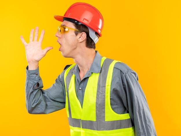 Zaniepokojony stojący w widoku profilu młody budowniczy mężczyzna w mundurze w okularach wzywający kogoś