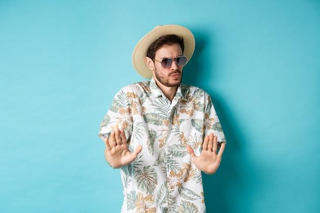 Zaniepokojony turysta proszący o trzymanie się z daleka, cofnięcie się przed czymś kuli, pokazujący gest odrzucenia, stojący w słomkowym kapeluszu i hawajskiej koszuli, niebieskie tło.