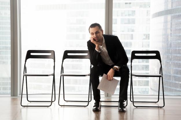 Zanudzony młody człowiek w garniturze siedzi w poczekalni.