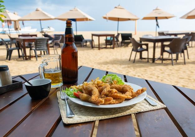 Zanurz smażone krewetki z frytkami i surówką. przekąski na piwo w restauracji przy plaży