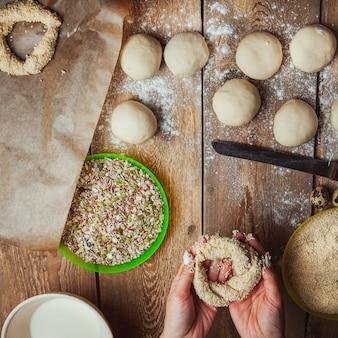 Zanurzać ciasto w sezamie kobietą przy piekarnia odgórnym widokiem