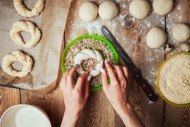 Zanurzanie skręconego ciasta w mieszance nasion przez widok z góry kobiet.