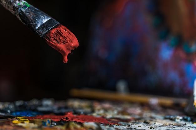 Zanurzanie starego pędzla w czerwonym kolorze