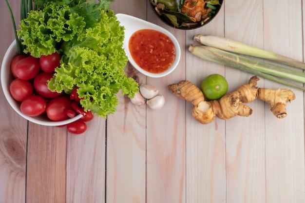 Zanurzenie, trawa cytrynowa, czosnek, limonka, galanga, pomidor i sałatka na drewnianej podłodze