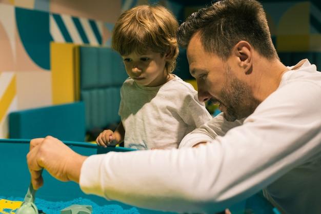 Zanurzenie w procesie twórczym przy użyciu piasku kinetycznego dla taty i syna odbywa się w centrum rozwoju. rozwój umiejętności motorycznych. terapia sztuką. łagodzenie stresu i napięcia. kreatywność.