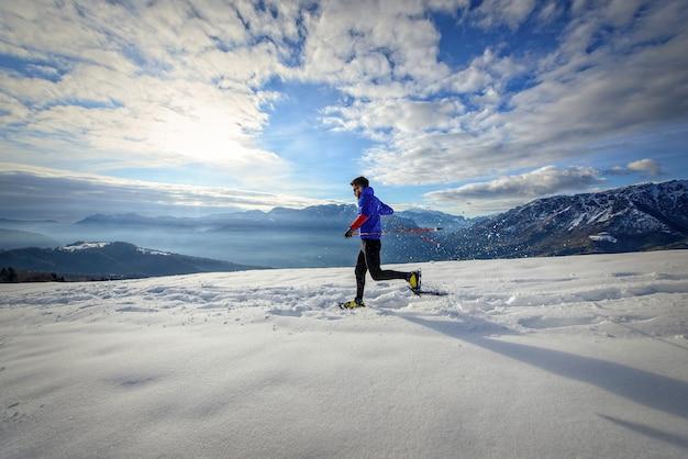 Zanurzony w alpejskiej przyrodzie z rakietami śnieżnymi o zachodzie słońca